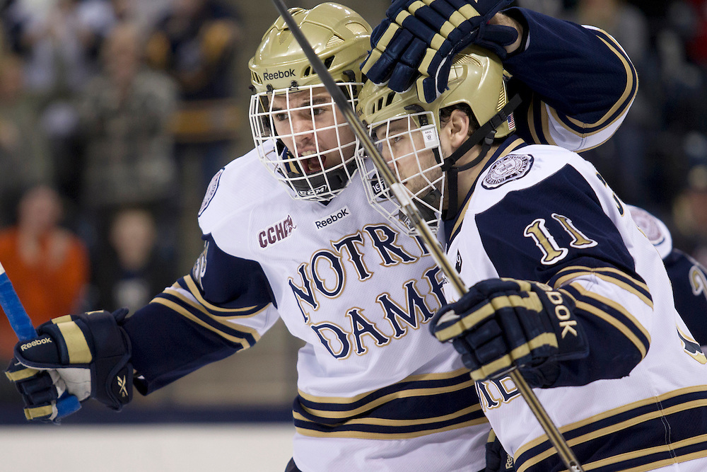 Notre Dame defenseman Kevin Lind (#25) and Notre Dame left wing Jeff Costello (#11) celebrate first period goal in action of NCAA hockey game between Notre Dame and Ohio State.  The Notre Dame Fighting Irish defeated the Ohio State Buckeyes 4-2 in game at the Compton Family Ice Arena in South Bend, Indiana.