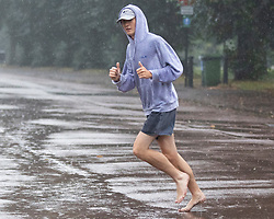 © Licensed to London News Pictures. 14/09/2021. London, UK. A man gives a thumbs up as he jogs barefoot during heavy rain in Greenwich Park, South East London . A yellow weather warning for rain is in place in parts of England . Photo credit: George Cracknell Wright/LNP