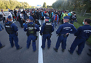 Hungarian police try to contain migrants as they broke out from the camp and joined the motorway and started walking towards Budapest close to the Hungarian and Serbian border town of Roszke, Hungary, September 7 2015. The UN's humanitarian agencies are on the verge of bankruptcy and unable to meet the basic needs of millions of people because of the size of the refugee crisis in the Middle East, Africa and Europe, senior figures within the UN have told the media.