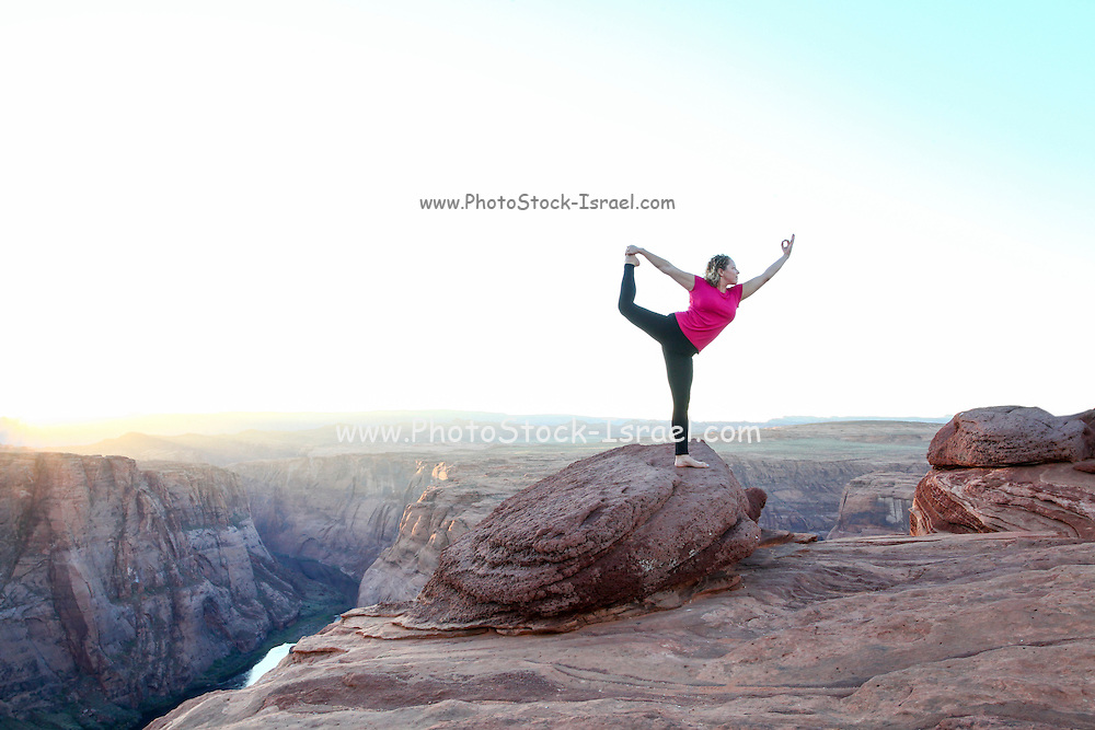 Young woman doing Yoga at Horseshoe Bend Colorado River Arizona USA