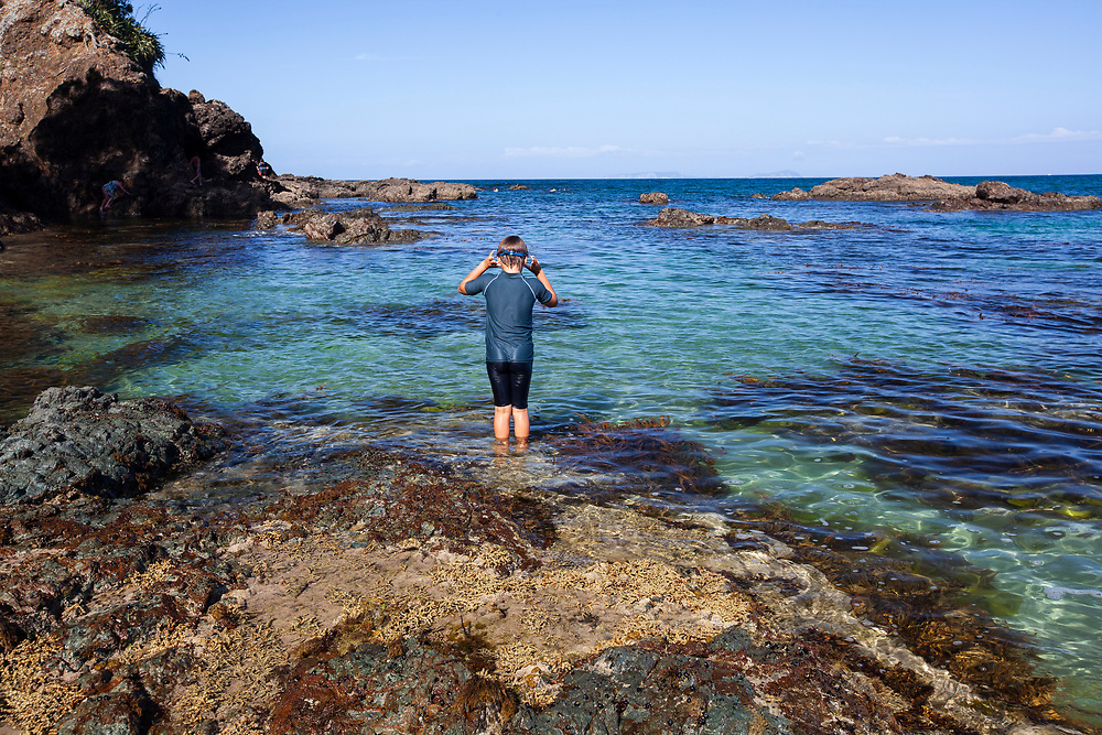 Young boy about to enter clear tidal pools at Moureeses Bay, Northland