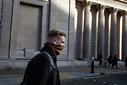 A man with his face covered by a scarf crosses the road in front of the Bank of England in what would normally be the morning rush hour in the City of London on March 17th, 2020. The financial district of the UK is unusually quiet after the government requested people to refrain from all but essential travel and activities yesterday.