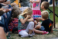Children in the section reserved for immediate family of the 19 firefighters killed in a nearby wildfire wait before a prayer vigil ceremony in Prescott, Arizona July 2, 2013. REUTERS/Rick Wilking (UNITED STATES)