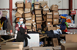 18 November 2020. Care4Calais - Calais, France.<br /> Care4Calais warehouse. Coats and clothes, all cleaned, pre sorted and checked to ensure they are in good condition are packed by volunteers ready for later distribution to desperate migrant refugees - many of whom have little in the way of warm clothing as winter approaches. <br /> Claire Moseley, founder of the British volunteer run refugee charity Care4Calais works tirelessly to build her foundation  to help migrant refugees as they struggle to survive on the streets of Calais where they are constantly harassed and moved on by authorities. Care4Calais provides meals, clothing, haircuts, charging stations for phones, medical aid, hot drinks, tents, blankets and a wide range of goods and services.<br /> Photo©; Charlie Varley/varleypix.com