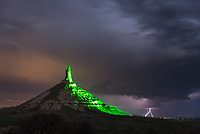 When this evening thunderstorm popped up, I knew I had to go to Chimney Rock to try to shoot the lightning behind it. After taking over 100 pictures, I eventually caught a couple bolts. A green light shines on the rock formation all night long.
