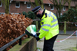 © Licensed to London News Pictures. 26/01/2021. London, UK. A police officer with floral tributes on Holland Walk in Islington, north London after a fatal stabbing of a teenage boy. Police were called to Holland Walk on Monday 25 January at approximately 17:30GMT to a report of a stabbing. Officers attended with London Ambulance Service and helicopter emergency medical service (HEMS), and found a teenage boy suffering from a stab injury. Despite efforts by emergency services he was sadly pronounced dead at the scene a short while later. Photo credit: Dinendra Haria/LNP