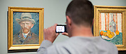 Visitor photographs on smartphone self portrait by Vincent Van Gogh at Rijksmuseum, Amsterdam, Holland