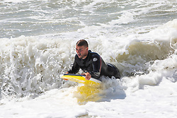 © Licensed to London News Pictures. 28/07/2016. Brighton, UK. Surfers take advantage of the strong winds and powerful waves to take part in the hobby in Brighton and Hove. Photo credit: Hugo Michiels/LNP