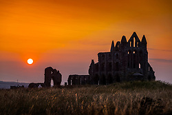 © Licensed to London News Pictures. 22/07/2021. Whitby UK. The sun sets behind the gothic ruins of Whitby abbey in Yorkshire last night ending another hot day in the UK. Photo credit: Andrew McCaren/LNP