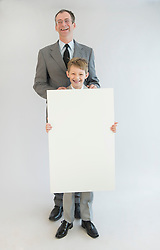 Father and son holding blank whiteboard, smiling, portrait