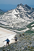 """Hikers ascend snowfields on Tsouka Rossa Pass on the Tymfi Massif, north Pindus Mountains (Pindos or Pindhos), Zagoria, Epirus/Epiros, Greece, Europe. Mount Tymfi (or Greek: , also transliterated Timfi, Tymphe, or Tymphi) forms a massif with its highest peak, Gamila, at 2497 meters (8192 feet), the sixth highest in Greece. Zagori (Greek: ) is a region and a municipality in northwestern Greece containing 45 villages collectively known as Zagoria (Zagorochoria or Zagorohoria). Published in """"Pindos: The National Park"""" (2010) by Alexander G. Tziolas, preface by Tom Dempsey et al, ISBN 978-960-98795-3-8."""