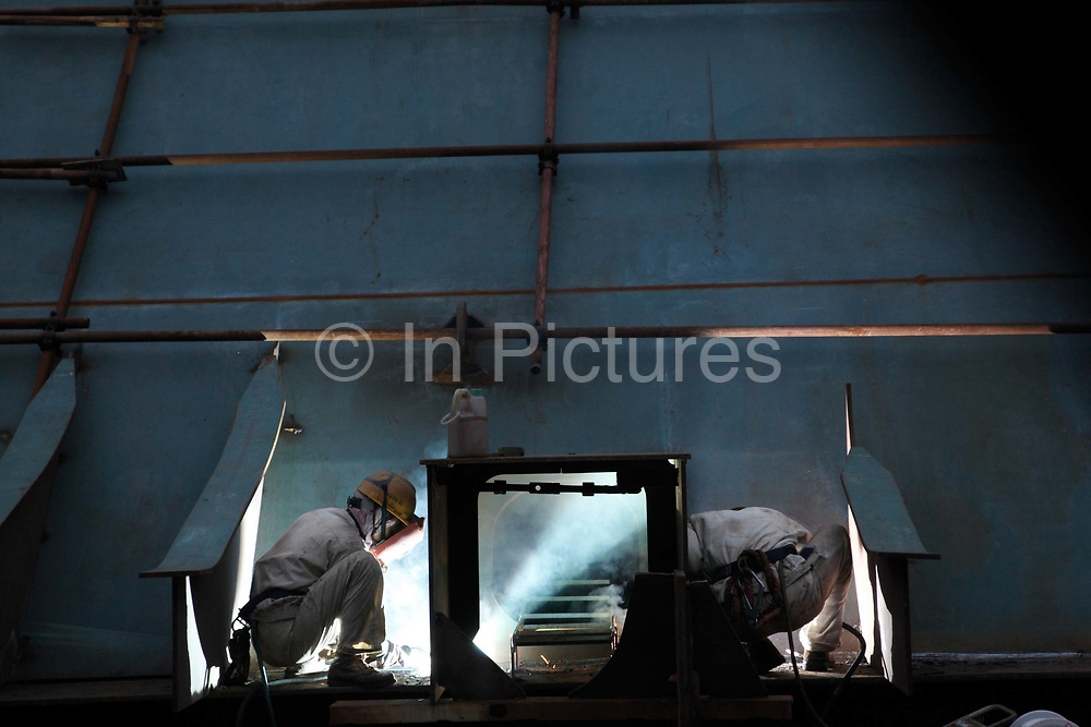 Welders at work at the China CSSC Holdings Ltd. Chengxi Shipyard in Jiangyin, China, on Sunday, Sept. 12, 2010. China CSSC Holdings Ltd., the nation's biggest shipyard, sees orders surge as China's voracious appetite for commodities demands more fleets of large vessels.