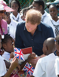 Eight-year-old Akia Slocombe (left) shows Prince Harry a picture of her father Tim, who was injured while serving in Afghanistan, as he takes part in a community sports event at Queens Park Grounds in Grenada during the second leg of his Caribbean tour.