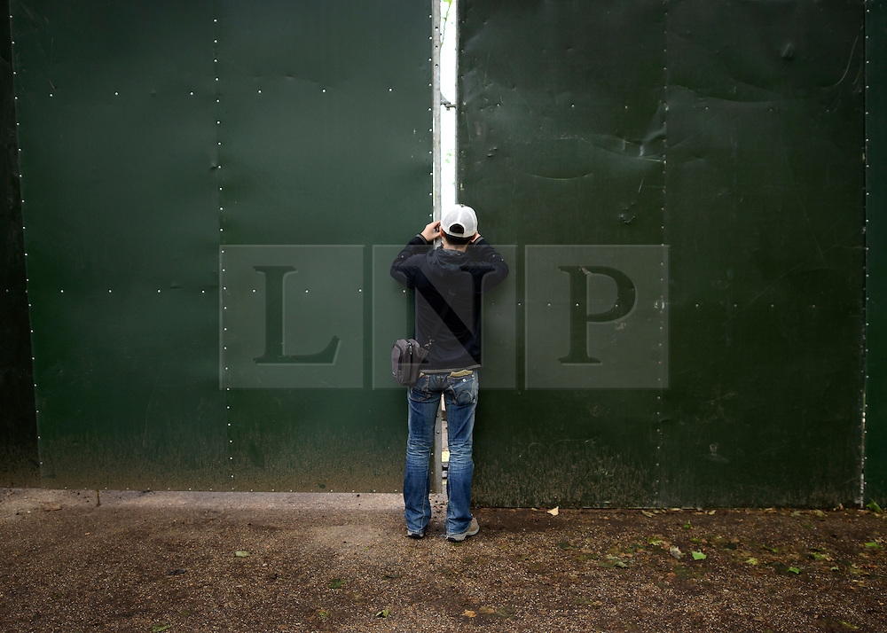 © Licensed to London News Pictures. 06/06/2012. London, UK. A man takes a photograph through a security wall into the construction site in front of Buckingham Palace. Workmen begin the task of deconstructing the stages and scaffolding platforms put in place for the celebrations.  The Royal Jubilee celebrations. Great Britain is celebrating the 60th  anniversary of the countries Monarch HRH Queen Elizabeth II accession to the throne this weekend Photo credit : Stephen Simpson/LNP