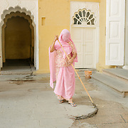 A woman cleaning while wearing a pink sari. Mehrangarh or Mehran Fort, one of the largest forts in India. Jodhpur is known as the Blue City.