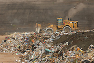 A bulldozer operator moves trash before covering it with soil at a landfill near Orlando, Florida.