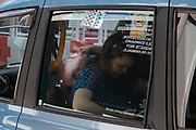 Reflection of a mysterious face in the window of a passing taxi on 10th August 2021 in London, United Kingdom. the eye looking back is from a fashion retailer advertisement and interacts with the taxis passenger who is busy on her phone.