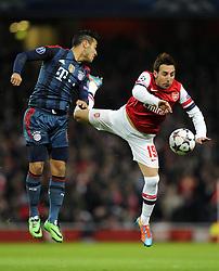 Bayern Munich's Thiago Alcantara battles for the high ball with Arsenal's Santi Cazorla - Photo mandatory by-line: Joe Meredith/JMP - Tel: Mobile: 07966 386802 19/02/2014 - SPORT - FOOTBALL - London - Emirates Stadium - Arsenal v Bayern Munich - Champions League - Last 16 - First Leg