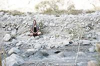 Wild Woman meditating in desert wilderness nature.