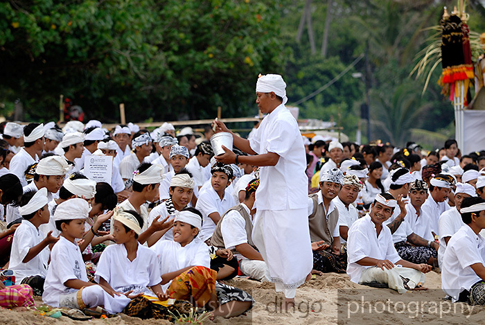 Pemangku. or local priest, splashing holy water during Galungan, a Hindu religious ceremony. Galungan celebrates the victory of virtue (Dharma) over evil (Adharma) and is the most important religious holiday for Balinese Hindus. Sanur, Bali, Indonesia
