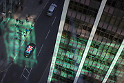 Looking down from an aerial view towards green reflected light and a passing taxi cab with a union Jack flag on its roof with passing business figures walking through the City of London, the capitals ancient financial district, on 13th May, in London, England.
