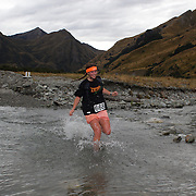 Runner Molly Doell crosses  Moke Creek on the Ben Lomond High Country Station during the Pure South Shotover Moonlight Mountain Marathon and trail runs. Moke Lake, Queenstown, New Zealand. 4th February 2012. Photo Tim Clayton
