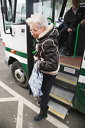 Elderly woman with Cerebral Palsy getting off specialised transport  for people with physical and sensory impairment.