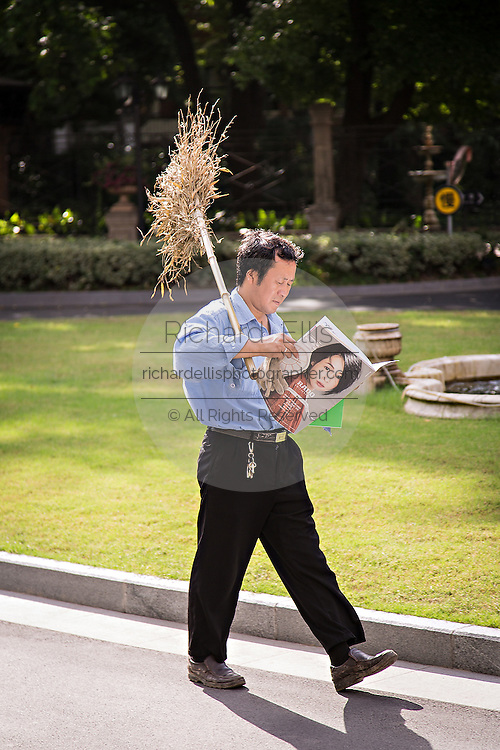 A Chinese workman carrying a broom reads a modern glossy magazine as he walks in Shanghai, China