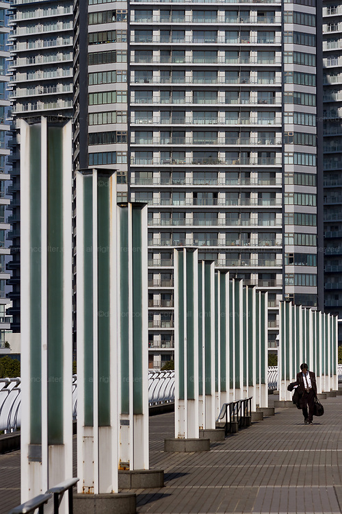 A salaryman or Japanese office worker walks in front of apartment buildings in Minato Mirai, Sakuragicho, Yokohama, Japan. Saturday March 2nd 2019