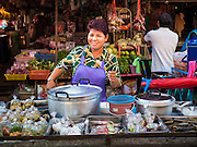 """12 JUNE 2015 - BANGKOK, THAILAND: A congee vendor in Khlong Toey Market in Bangkok. Congee is rice porridge popular in Southeast Asia. Khlong Toey (also called Khlong Toei) Market is one of the largest """"wet markets"""" in Thailand. The market is located in the midst of one of Bangkok's largest slum areas and close to the city's original deep water port. Thousands of people live in the neighboring slum area. Thousands more shop in the sprawling market for fresh fruits and vegetables as well meat, fish and poultry.          PHOTO BY JACK KURTZ"""