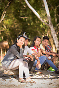 Group of people sat on log looking to camera, Red Island Beach, Red Island, Banyuwangi Regency, East Java, Indonesia, Southeast Asia