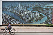 "A man bikes past a large artist's depiction of the Binhai New Development Zone's Yujiapu and Xiangluowan districts in Tianjin, China on 16 July 2013. The districts had the ambition of becoming China's newest financial center and dubbed by some ""the Manhattan of the East"",  however as the country tries to steer away from an investment driven economy, such projects are facing increasing scrutiny."