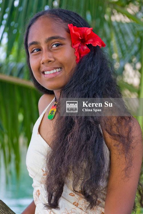 Girl in traditional dress with palm tree, Palau