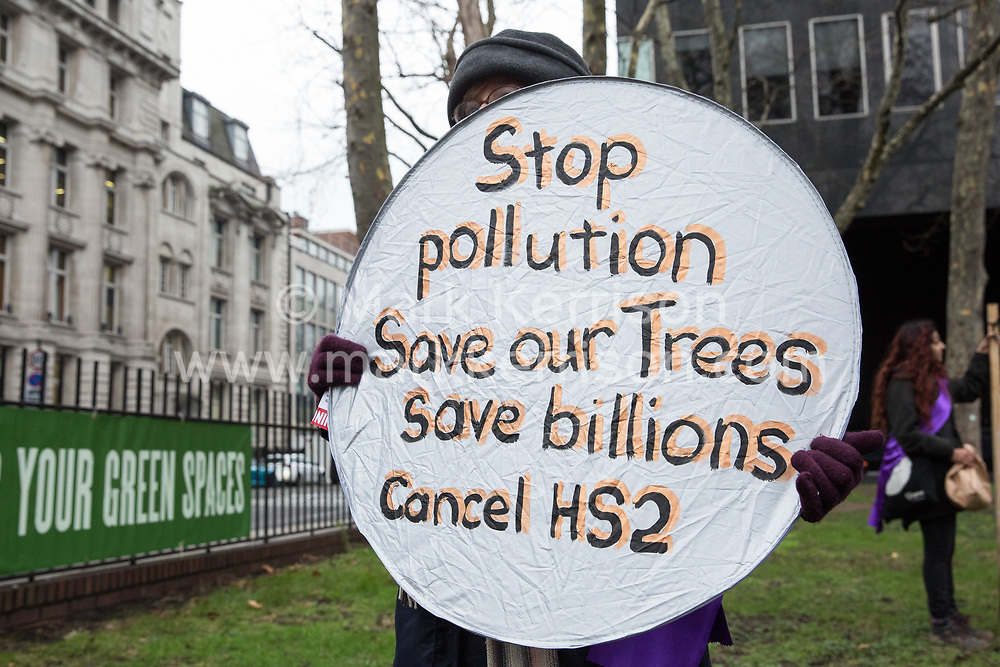 London, UK. 12th January, 2018. An activist stands holding an anti-HS2 sign in Euston Square Gardens. Local residents and environmental campaigners are protesting against the planned felling of mature London Plane, Red Oak, Common Whitebeam, Common Lime and Wild Service trees in Euston Square Gardens to make way for temporary sites for construction vehicles and a displaced taxi rank as part of preparations for the HS2 high-speed rail line.