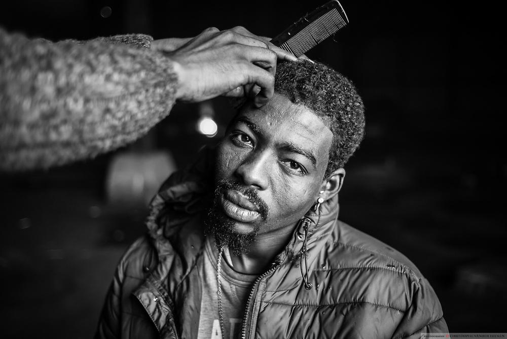 Calais, France, 6 Januari 2015.  A Sudanese refugee is having a haircut at squat Galloo.