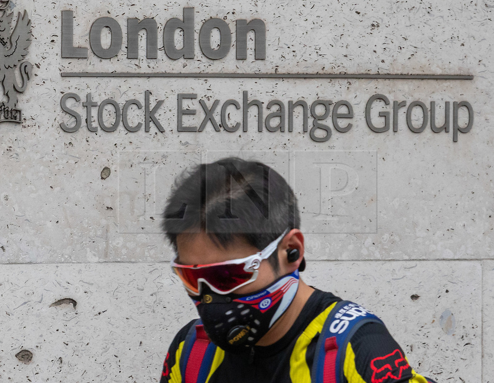 © Licensed to London News Pictures. 09/03/2020. London, UK. A man with a protective mask walks past the London Stock Exchange today as markets around the world plunge as fears over the Coronavirus disease continues. Photo credit: Alex Lentati/LNP
