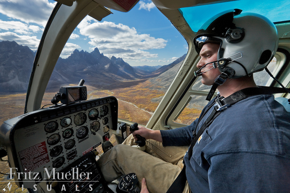 Helicopter pilot flies down Tombstone Valley with Tombstone Mountain beyond