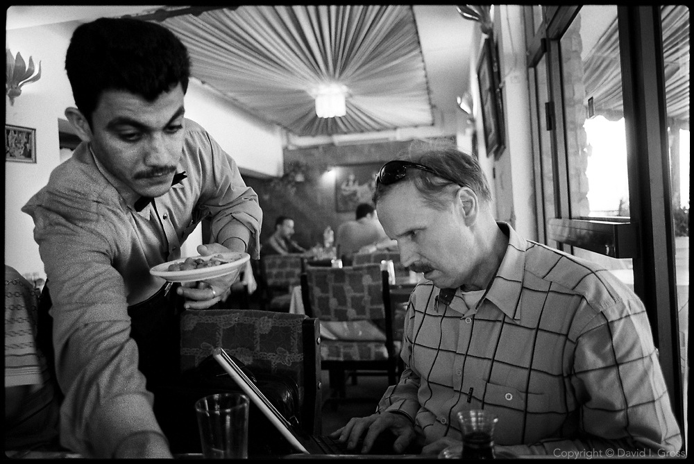 Alexander (Sasha) Petrov, the Chechnya researcher of Human Rights Watch, has come to Iraq to help document current and past human rights abuses. He is checking his computer as he eats lunch in a Baghdad restaurant.