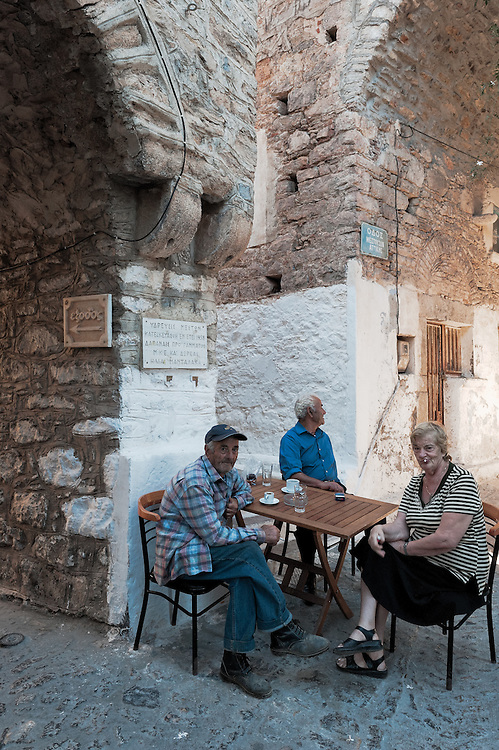 There villagers drink their morning coffee under the arches of the narrow alleys of Mesta village in Chios island, Greece.