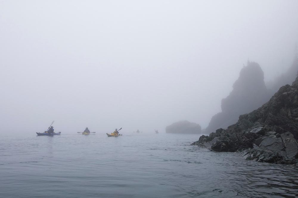 Sea kayakers paddle through the fog in Lake Superior Provincial Park near Wawa Ontario Canada.