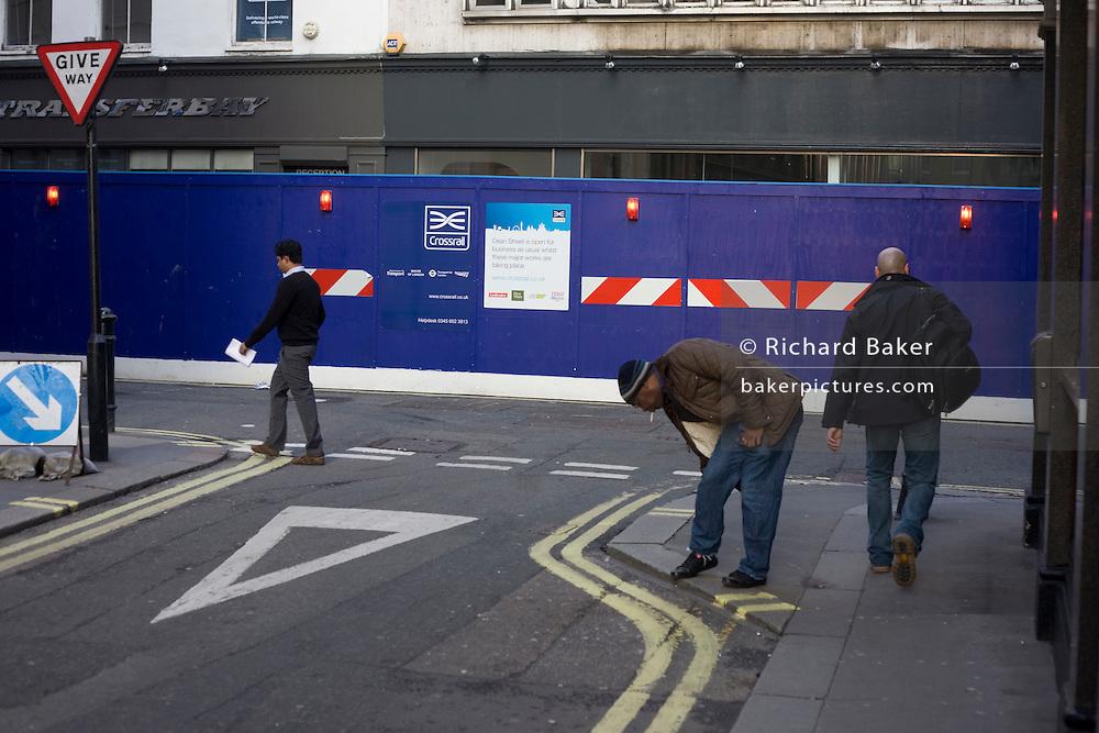 Pedestrians walk over road junction near Crossrail construction site.