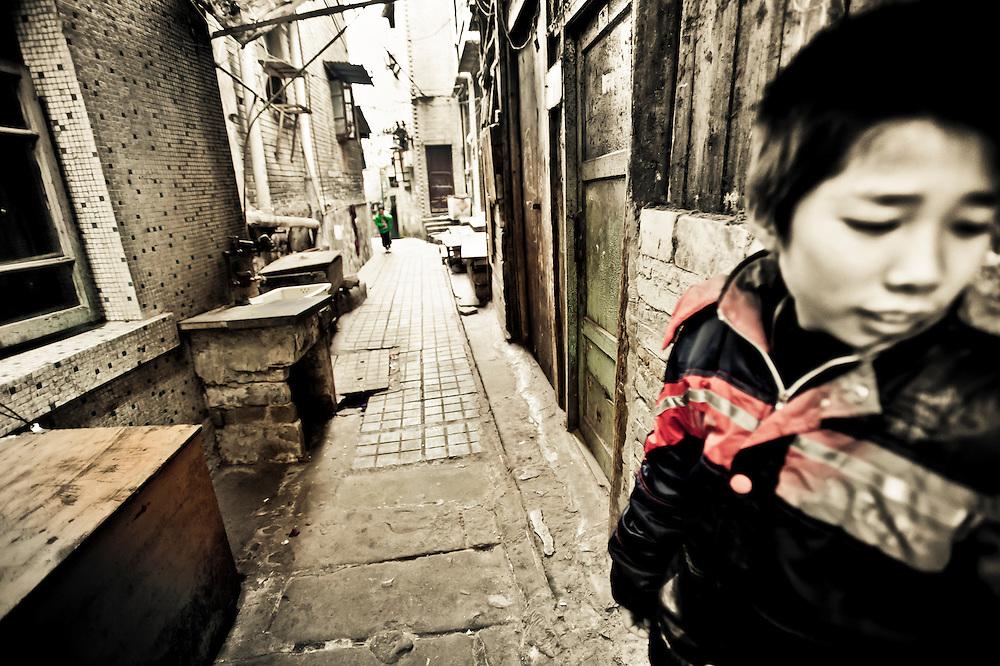 Chongqing - 7 gennaio 2011: un ragazzino in un vicolo stretto a Chaotianmen. La sua famiglia ancora non sa se e quando il governo della città deciderà di demolire l'area.     Chongqing - January 7, 2011: a young boy in a hutong in Chaotianmen. His family doesn't know yet if and when the government will ever decide to demolish the area where they live.