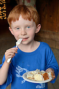 Young boy eating cake.