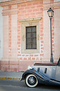Vintage car on city street with building in background, Cadiz, Andalusia, Spain