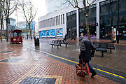 National coronavirus lockdown three begins in Birmingham city centre, which is deserted apart from a lone figure carrying a Union Jack flag shopping bag and walking slowly with the help of a crutch along New Street on 6th January 2021 in Birmingham, United Kingdom. Following the recent surge in cases including the new variant of Covid-19, this nationwide lockdown, which is an effective Tier Five, came into operation today, with all citizens to follow the message to stay at home, protect the NHS and save lives.