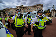 """Police obstructing members of the press to do their job outside the Buckingham Palace after they arrested an Animal and climate activist from Animal Rebellion because they dyed blood-red Buckingham Palace fountains on Thursday, Aug 26, 2021 - signifying as their statement said """"its' demonstrable role in hunting and animal agriculture"""". (VX Photo/ Vudi Xhymshiti)"""