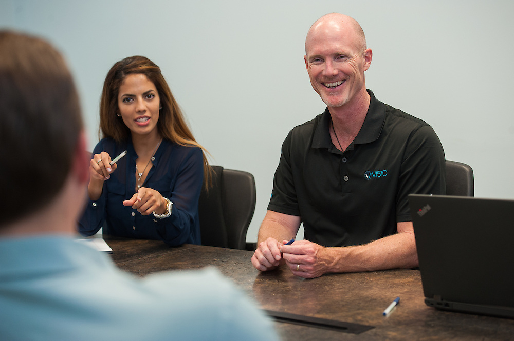 Jeff Ball, President and CEO of Visio Financial Services ( right) joins in a meeting with Martha Barreda, Account Executive, and others in the company conference room.