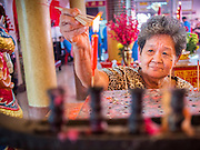 """09 FEBRUARY 2014 - HAT YAI, SONGKHLA, THAILAND:  A woman lights candles in the Chao Mae Tubtim Shrine (Ruby Goddess Shrine) on 108 Hainanese Ancestors Memorial Day in Hat Yai, Songkhla, Thailand. Hainanese communities around the world celebrate """"108 Hainanese Ancestors Memorial Day."""" The day honors the time when 109 Hainanese villagers fleeing life in Hainan (an island off of the southwest coast of China, near Vietnam) washed up in what is now Vietnam and were killed by Vietnamese authorities because authorities thought they were pirates. The Vietnamese built a temple on the site and named it """"Zhao Yin Ying Lie."""" Many Vietnamese fisherman credit prayers at the temple to saving their lives during violent storms and now """"108 Hainanese Ancestors Memorial Day"""" is celebrated in Hainanese communities around the world. Hat Yai, the economic center of southern Thailand has a large Hainanese population.   PHOTO BY JACK KURTZ"""