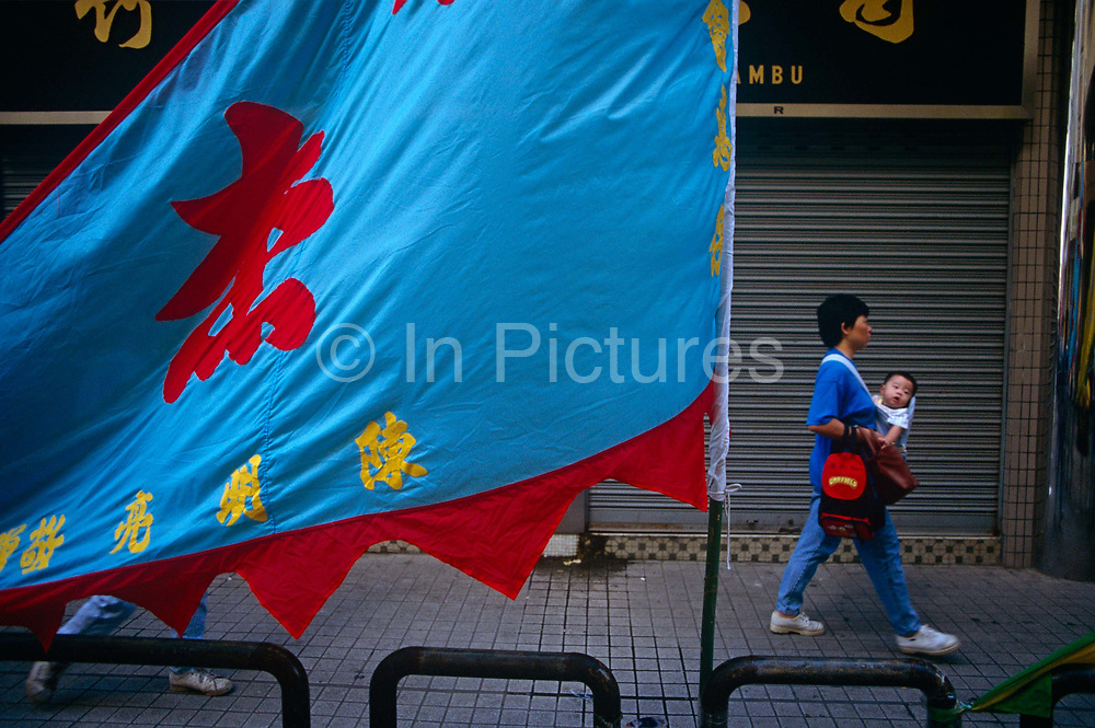 A Chinese mother carries her baby in a sling on her chest, passing a colourful banner on a Macau street, China in this ex-Portuguese colony. After emerging from a crowded morning market, the lady and her child pass-by during the rainy season.  Macau is now administered by China as a Special Economic Region (SER) and is home to a population of mainland 95% Chinese, primarily Cantonese, Fujianese as well as some Hakka, Shanghainese and overseas Chinese immigrants from Southeast Asia and elsewhere. The remainder are of Portuguese or mixed Chinese-Portuguese ancestry, the so-called Macanese, as well as several thousand Filipino and Thai nationals. The official languages are Portuguese and Chinese.
