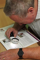 Patient using illuminated magnifier to look at brochure in consulting room in eye clinic at QMC hospital, Nottingham.